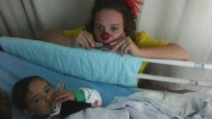 Yirmi playing harmonica with hospital clown